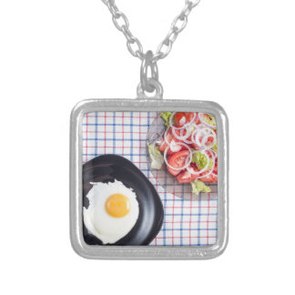 Top view on a black plate with a fried egg silver plated necklace