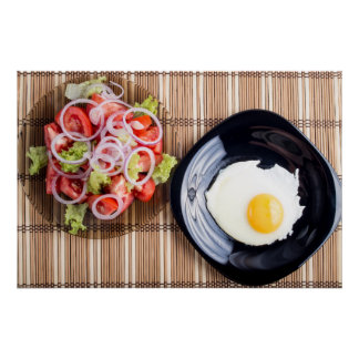 Top view on a fried egg and a salad of tomato poster
