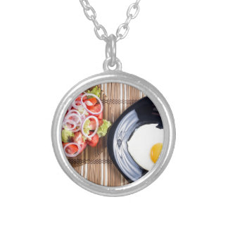 Top view on a fried egg and a salad of tomato silver plated necklace