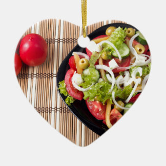 Top view on a healthy and natural vegetable salad ceramic heart decoration