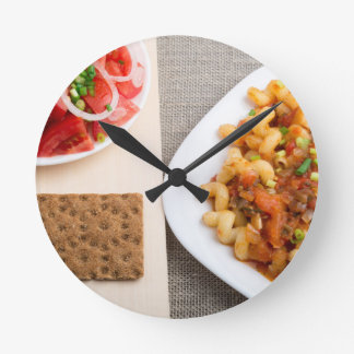 Top view on Cavatappi Pasta on textile background Round Clock