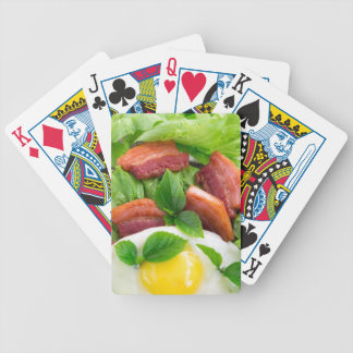 Top view on egg yolk, fried bacon and herbs bicycle playing cards