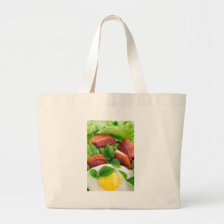 Top view on egg yolk, fried bacon and herbs large tote bag