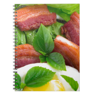 Top view on egg yolk, fried bacon and herbs notebooks