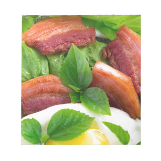 Top view on egg yolk, fried bacon and herbs notepad