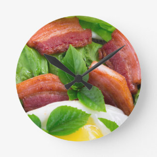 Top view on egg yolk, fried bacon and herbs round clock