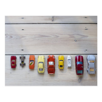 Toy cars lined up in a row on floor postcard