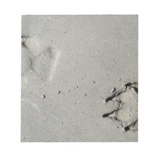 Tracks of a big dog on the sand notepad