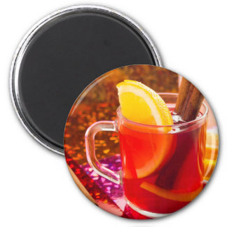 Transparent cup of tea with citrus and cinnamon magnet