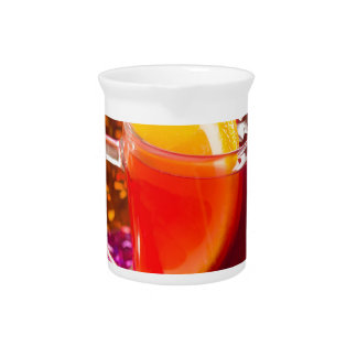 Transparent cup of tea with citrus and cinnamon pitcher