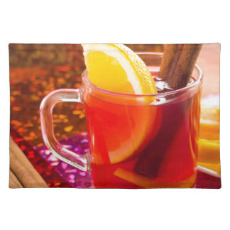 Transparent cup of tea with citrus and cinnamon placemat