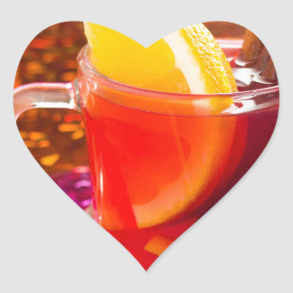 Transparent cup of tea with citrus, cinnamon heart sticker