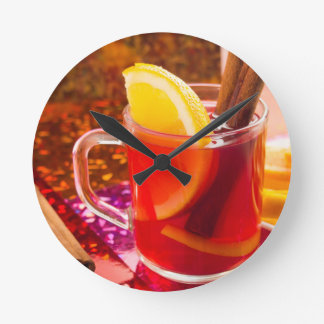 Transparent cup of tea with citrus, cinnamon round clock