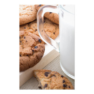 Transparent cup with milk and oatmeal cookies stationery