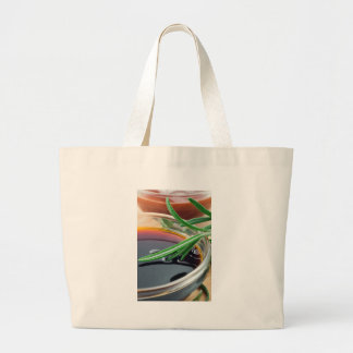 Transparent cup with soy sauce and rosemary leaves large tote bag