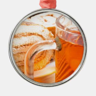 Transparent glass mug with hot tea and chocolate metal ornament