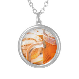 Transparent glass mug with hot tea and chocolate silver plated necklace