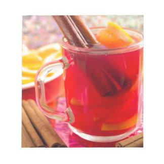 Transparent mug with citrus mulled wine, cinnamon notepad