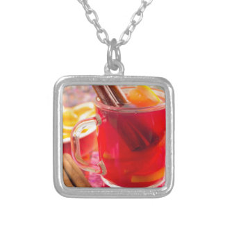 Transparent mug with citrus mulled wine, cinnamon silver plated necklace