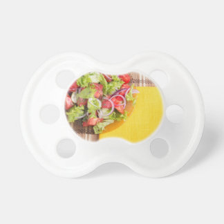 Transparent plate with fresh summer salad on a mat pacifiers