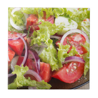 Transparent plate with vegetable salad closeup small square tile