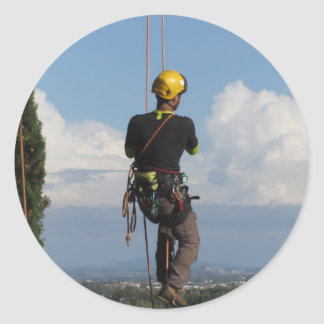 Tree surgeon lumberjack hanging from a big tree round sticker