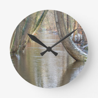 Tree trunks and forest stream  with snow in winter round clock