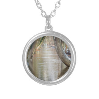 Tree trunks and forest stream  with snow in winter silver plated necklace