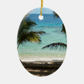 Tropical beach shaded by palms ceramic oval decoration