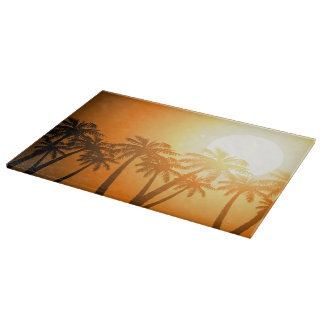 Tropical palm trees at sunset cutting board