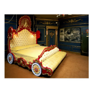 Tufted sleigh bed with wheels and a peacock postcard