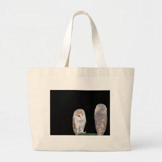Two barn owls isolated on dark background jumbo tote bag