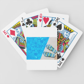 Two bathing slippers on edge of swimming pool bicycle playing cards