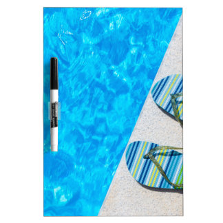 Two bathing slippers on edge of swimming pool dry erase whiteboard