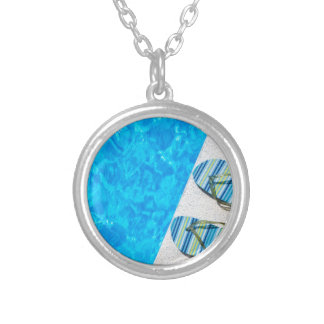 Two bathing slippers on edge of swimming pool silver plated necklace