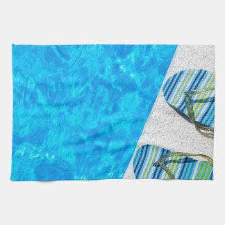 Two bathing slippers on edge of swimming pool tea towel