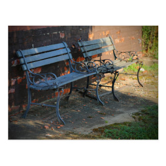 TWO BENCHES AGAINST A BROWN WALL POSTCARD