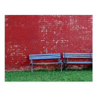 TWO BENCHES AGAINST A RED WALL POSTCARD