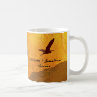 Two birds silhouetted against a golden red sky coffee mug