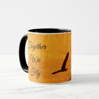 Two birds silhouetted against a golden red sky mug