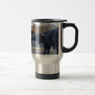 Two black scottish highlanders in frozen meadow travel mug