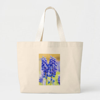 Two blue grape hyacinths in spring large tote bag