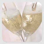 Two champagne flutes being filled with sparkling