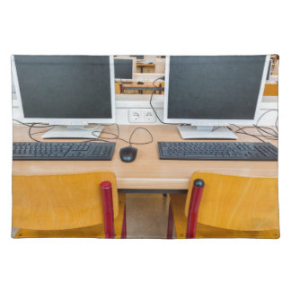 Two computers in classroom on high school place mat