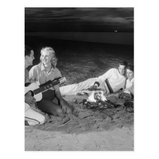 Two couples on beach sitting around campfire postcard