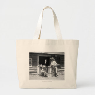 Two cowboys standing next to a barn with a horse large tote bag