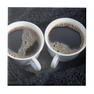 Two cups of coffee wrapped a black wool scarf ceramic tile