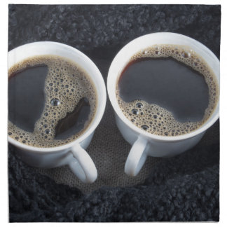 Two cups of coffee wrapped a black wool scarf napkin