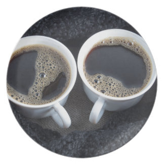 Two cups of coffee wrapped a black wool scarf plate