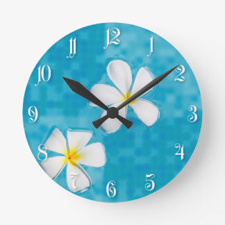 Two frangipani flowers in a blue water round clock